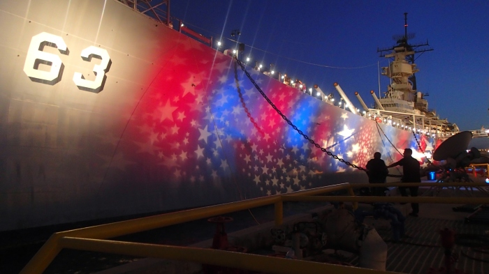 USS Missouri - with stars and stripes projected onto the hull at night.